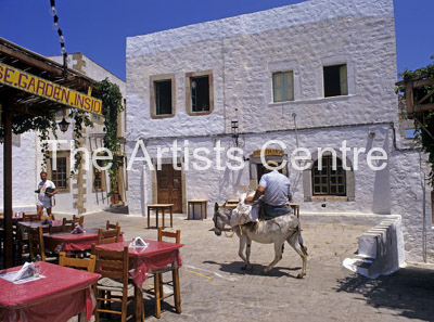 Man riding on small white Donkey in a village Greece Europe