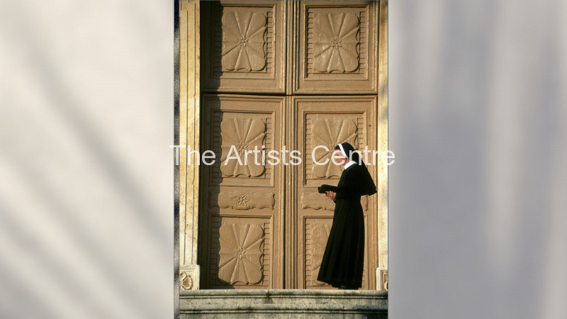 Nun by large wooden door