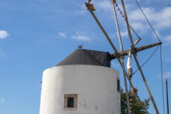 Cylindrical shaped blue and white windmill with a conical roof on hilltop Portugal