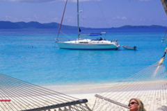 Woman relaxing in a hammock on beach with moored yacht  at White Bay Jost Van Dyke British Virgin Islands